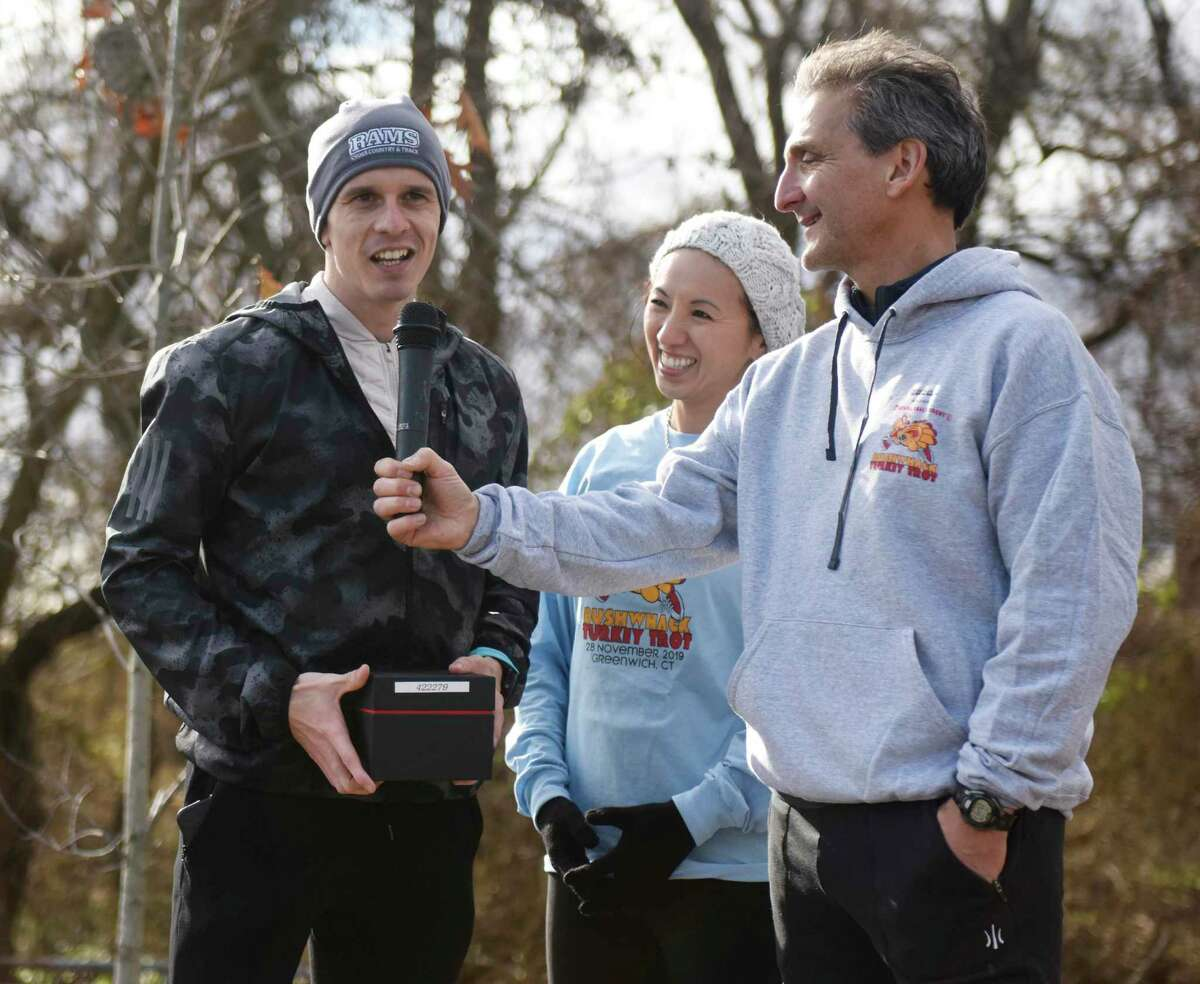 First-place finisher Milan Duka, left, thanks Dr. Janet Bodey, of Dental Oral Surgery, and Mickey Yardis, of Threads & Treads, at the 2019 Dental Oral Surgery Turkey Trot Beachfront Bushwhack at Greenwich Point Park in Old Greenwich, Conn. Thursday, Nov. 28, 2019. Presented by Dental Oral Surgery and Threads & Treads, 500 runners competed in the five mile cross-country race and kid's one mile fun run.