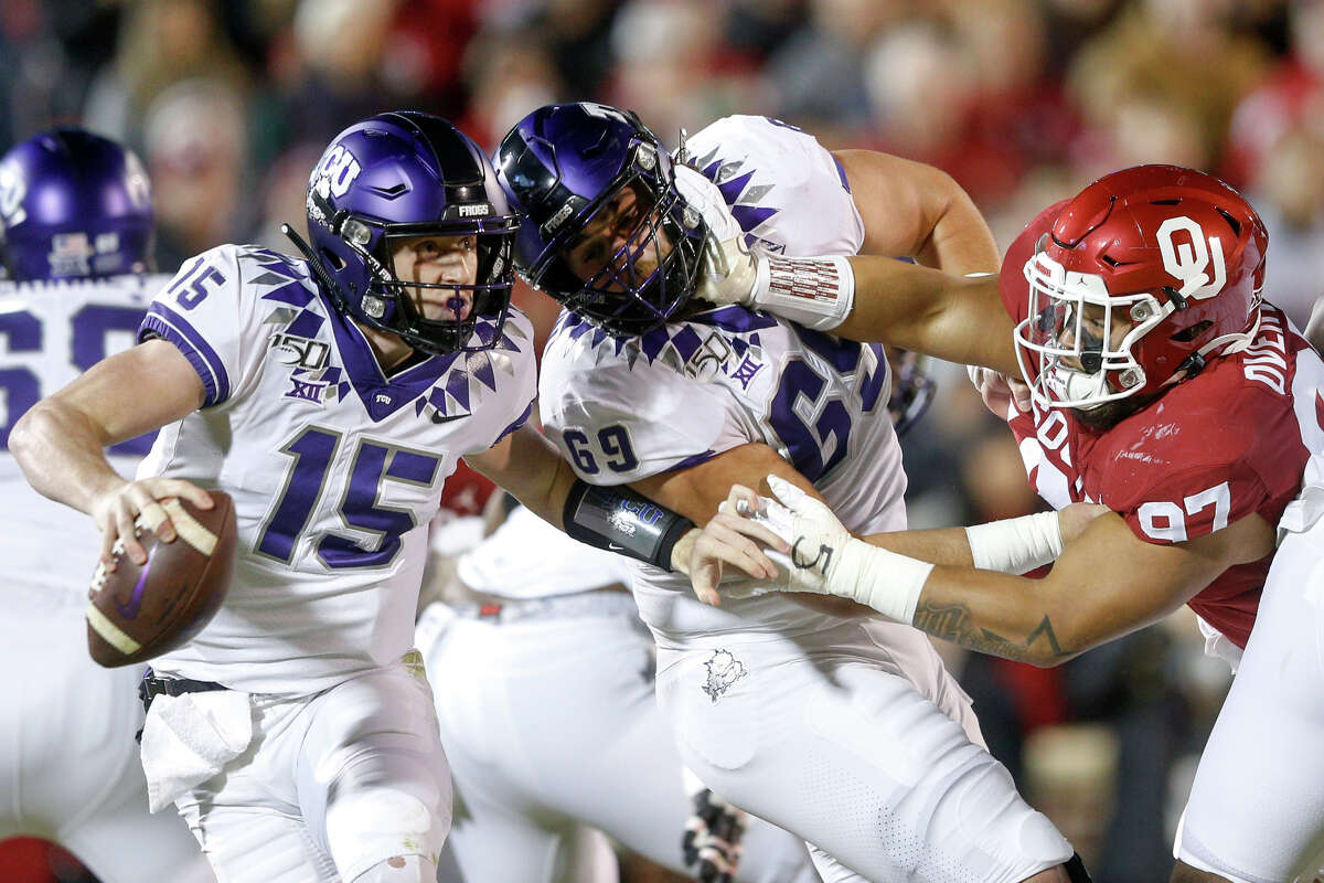 TCU quarterback Max Duggan (15) scramble s away as TCU center Coy McMillon (69) gets pushed back by Oklahoma defensive lineman Marquise Overton (97) during an NCAA college football game Saturday, Nov. 23, 2019, in Norman, Okla. (Ian Maule/Tulsa World via AP)