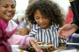 Tiana Herrera, center, 10, her sister Kiara, 3, second from left, and mother Carmen Herrera enjoy their meal at the 41st annual Big Super Feast at the George R. Brown Convention Center on Thursday, Nov. 28, 2019, in Houston. The family said it was their first time attending the feast, and that they heard about it because the mother works for W.I.C.