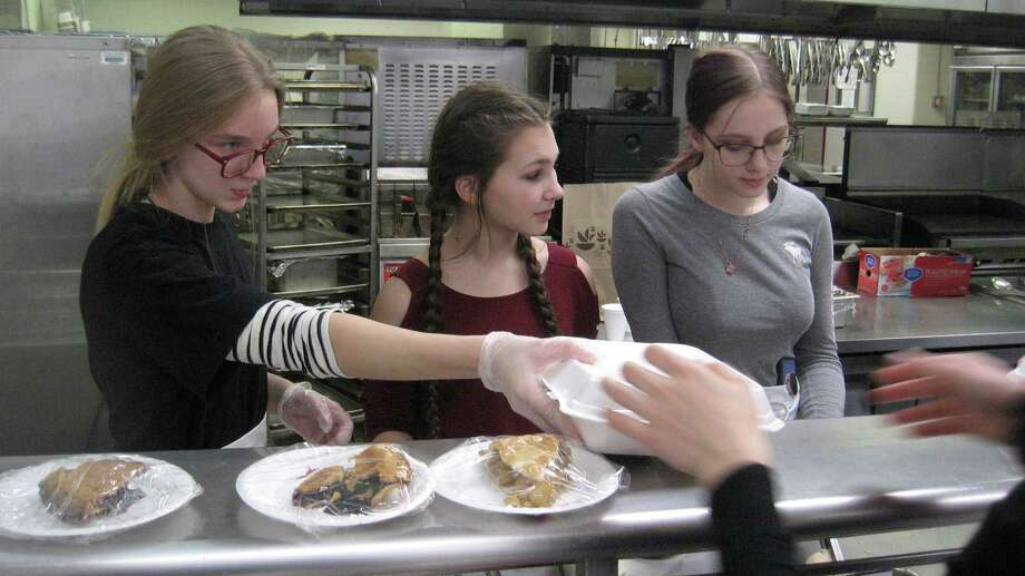 Dishing out the Thanksgiving dinners, from left, are OWTS students Abby Aria, Tabitha Langer and Haley Cogley. Photo: John Torsiello / For Hearst Connecticut Media /