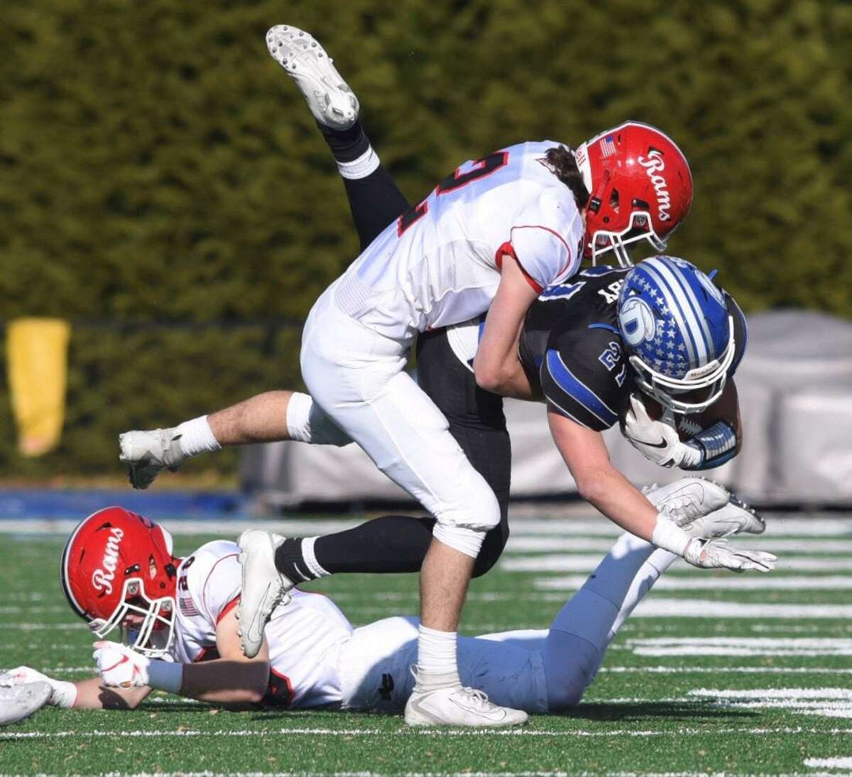 Darien's Will Kirby (21) is tackled by New Canaan's Jack Finningan (2) during the annual Turkey Bowl football game at Darien High School on Thursday, November 28, 2019.