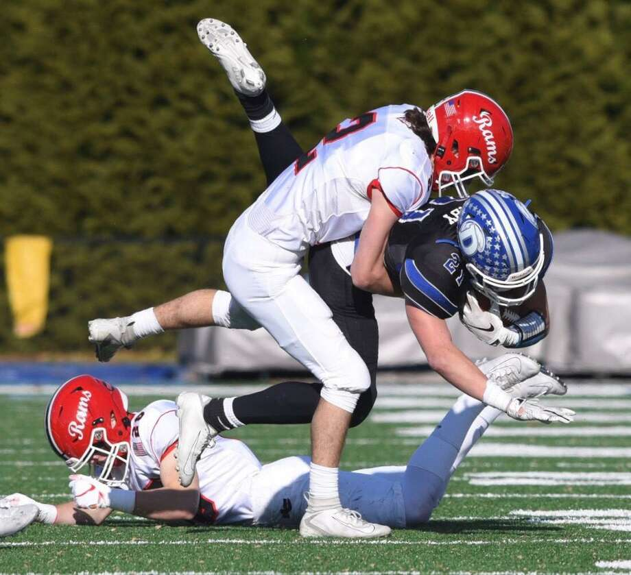 Darien's Will Kirby (21) is tackled by New Canaan's Jack Finningan (2) during the annual Turkey Bowl football game at Darien High School on Thursday, November 28, 2019. Photo: David Stewart / Hearst Connecticut Media / Connecticut Post