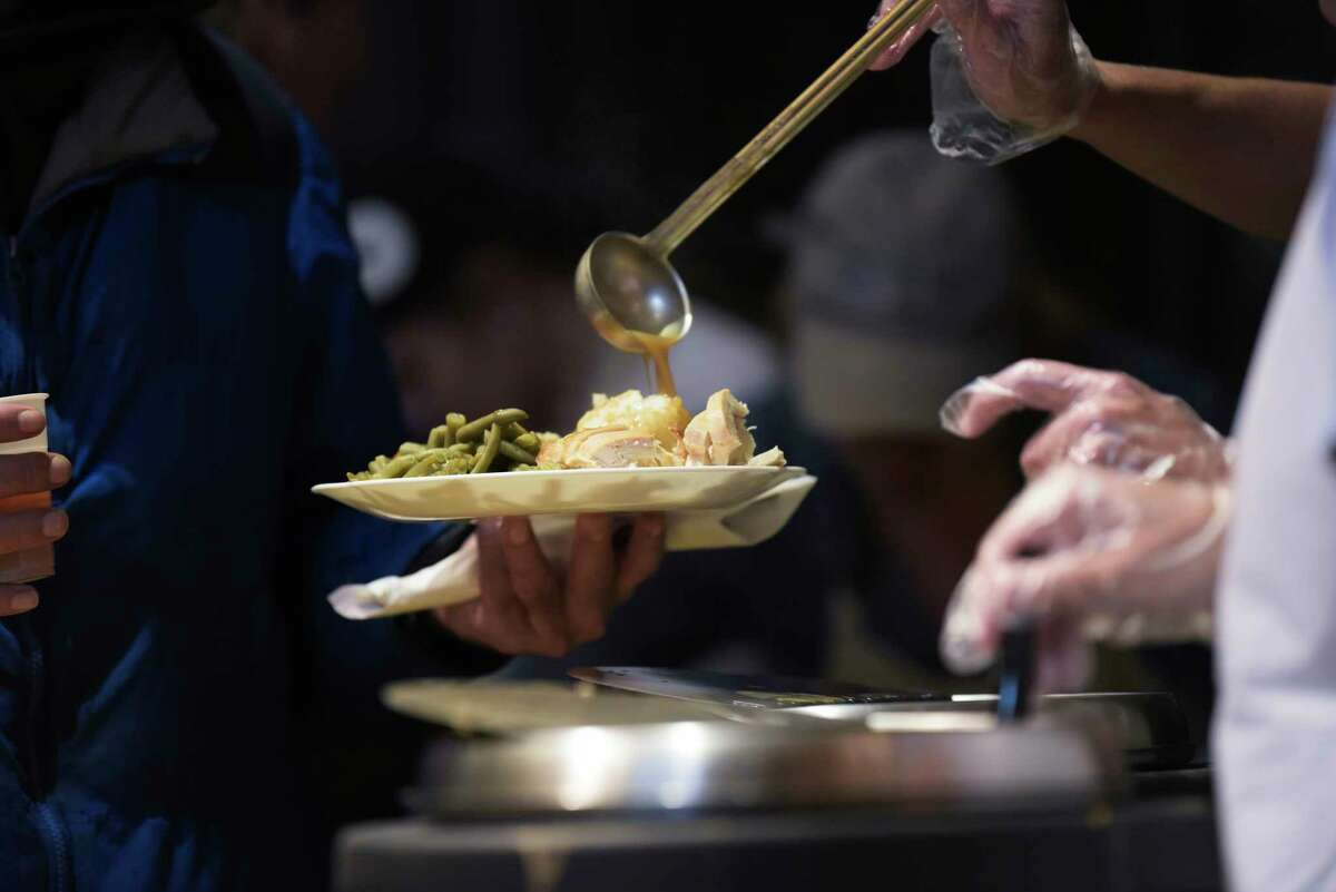 A volunteer puts gravy on a plate of food for a man taking part in the Equinox Thanksgiving Day Community Dinner at the First Presbyterian Church on Thursday, Nov. 28, 2019, in Albany, N.Y. (Paul Buckowski/Times Union)