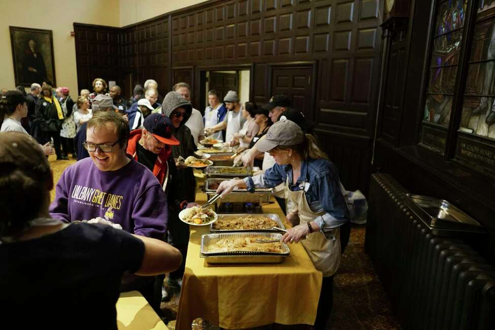 Volunteers serve up food to people attending the Equinox Thanksgiving Day Community Dinner at the First Presbyterian Church on Thursday, Nov. 28, 2019, in Albany, N.Y. (Paul Buckowski/Times Union)