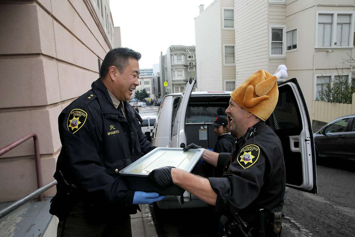"""San Francisco Sheriff-elect Paul Miyamoto, left, collects Thanksgiving food from Deputy Jason Tilton, San Francisco Sheriff's Office, at Lady Shaw Senior Center in San Francisco, Calif., on Thursday, November 28, 2019. The Thanksgiving Day event was a volunteer effort by the San Francisco Police Department, San Francisco Sheriff's Office, and the San Francisco Fire Department in conjunction with the Lady Shaw Senior Center. The organizations assembled and delivered Thanksgiving Day meals to people who are shut-in or don't have any family to share the holiday and a meal with. """"It's great,"""" Miyamoto said. """"It's a wonderful thing to do."""""""