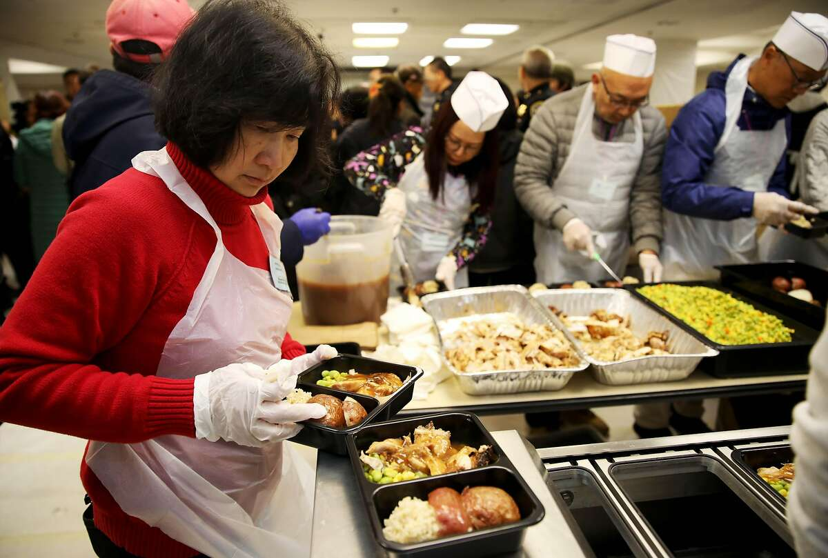 """Mabel Tse assembles a plate of Thanksgiving food at Lady Shaw Senior Center in San Francisco, Calif., on Thursday, November 28, 2019. The Thanksgiving Day event was a volunteer effort by the San Francisco Police Department, San Francisco Sheriff's Office, and the San Francisco Fire Department in conjunction with the Lady Shaw Senior Center. The organizations assembled and delivered Thanksgiving Day meals to people who are shut-in or don't have any family to share the holiday and a meal with. """"This is family,"""" Fred Lau, former San Francisco Police Chief, said. """"Thanksgiving is for all of us."""""""