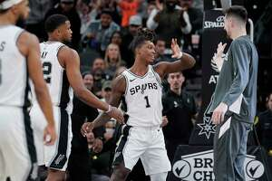 San Antonio Spurs' Lonnie Walker IV (1) is congratulated after scoring by teammates Rudy Gay, left, and Drew Eubanks during the second half of an NBA basketball game against the Minnesota Timberwolves, Wednesday, Nov. 27, 2019, in San Antonio. Minnesota won 113-101. (AP Photo/Darren Abate)