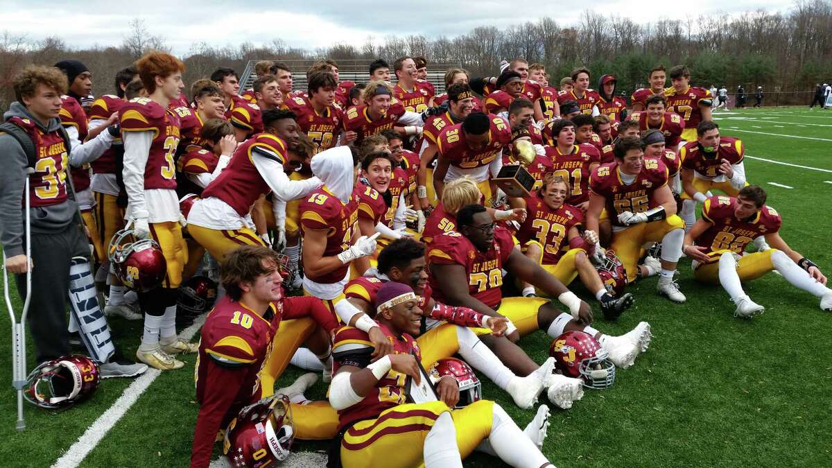 St. Joseph celebrates winning the Jerry McDougall Trophy with a 52-7 win over Trumbull at Dalling Field on Thursday.
