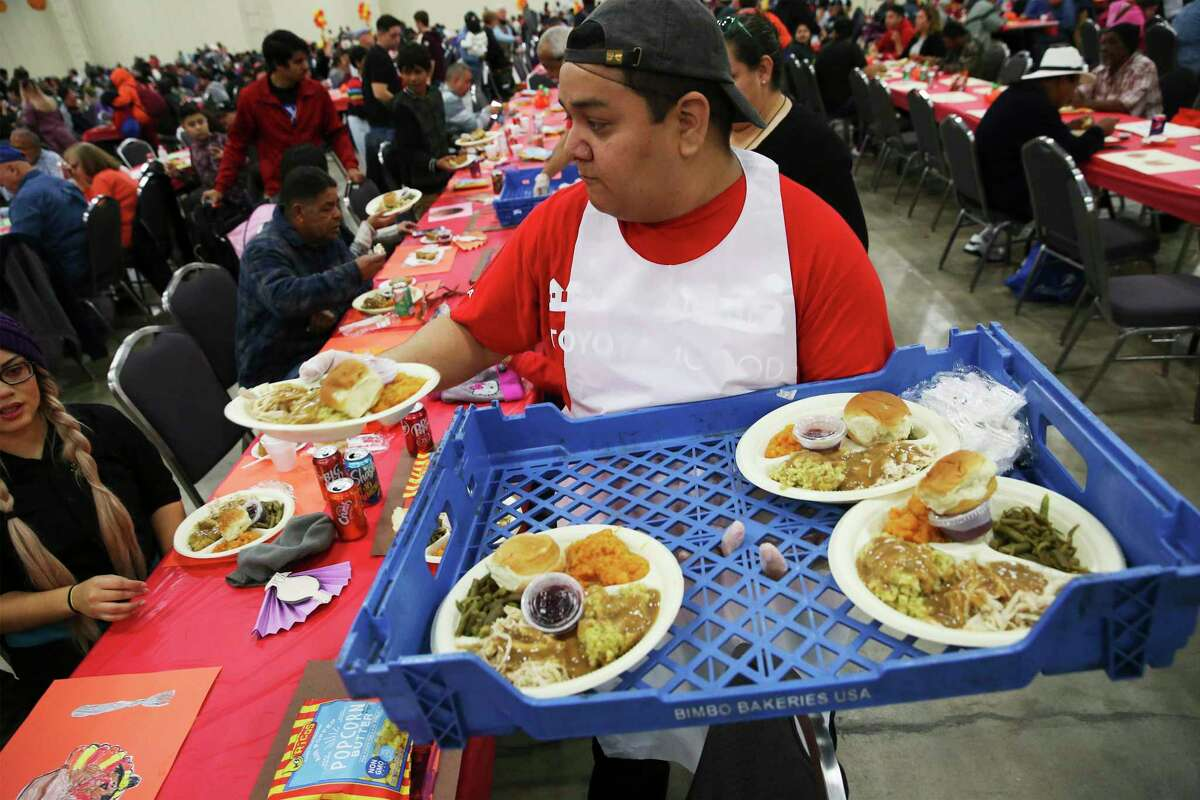 Volunteer Rey Guevara gives a plate of food to awaiting guests at the 40th annual Jimenez Thanksgiving dinner last year. that serves meals to thousands of guests at the Convention Center on Thursday, Nov. 28, 2019. The San Antonio tradition started by Restauranteur Raul Jimenez and continued by his daughter Patricia Jimenez offers a tasty Thanksgiving day meal to 22,000 people in attendance. The meal preparation started on Sunday where 550 turkeys were cooked along with thousands of pounds of yams and stuffing all handled by 5,000 volunteers. 3,000 meals were taken to people unable to attend the event. Musical performances and a dance floor allowed guests to dance off the meal before having a slice of pumpkin pie for dessert.
