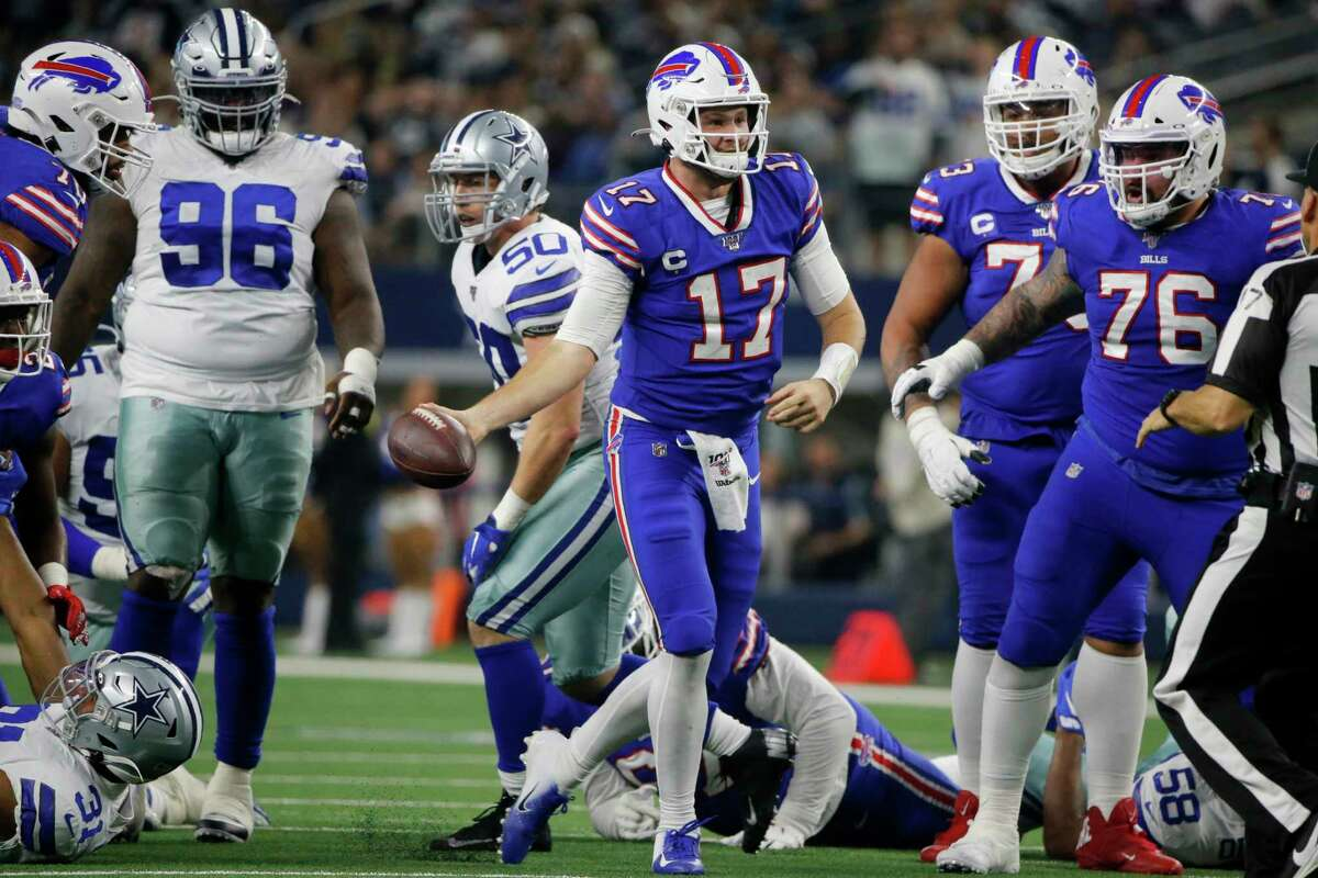 Buffalo Bills quarterback Josh Allen (17) celebrates after recovering a fumbled snap and getting a first down on the play in the first half of an NFL football game against the Dallas Cowboys in Arlington, Texas, Thursday, Nov. 28, 2019. The Cowboys' Maliek Collins (96) and Bills Jon Feliciano (76) look on during the play.