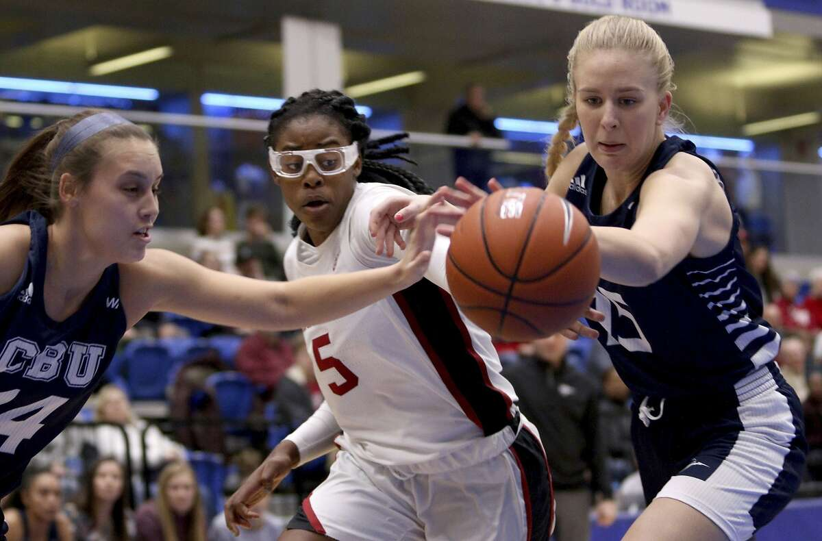 Stanford's Francesca Belibi, center, has the ball knocked away as California Baptist players, including Ragnheidur Einarsdottir, right, defend during the first half Thursday in Victoria, British Columbia.