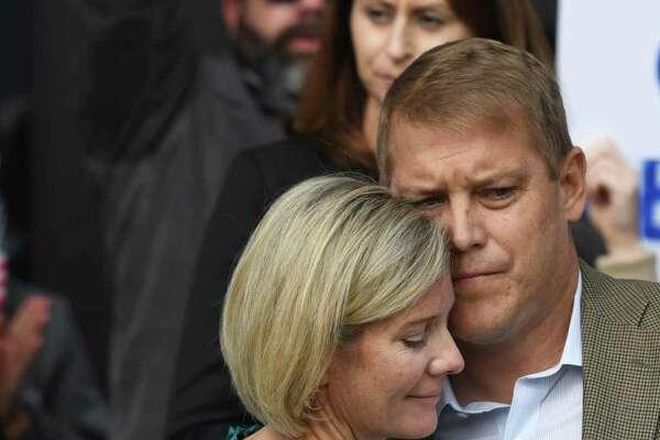 Darien's Scott Hapgood hugs his wife, Kallie Hapgood, at Town Hall in Darien, Conn. Monday, Oct. 28, 2019.