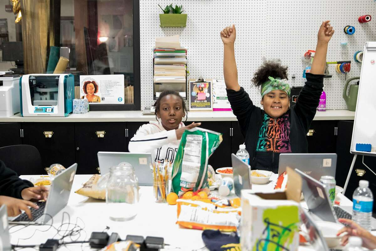 Donielle McGilberry, 11, raises her arms in celebration after completing 3,000 words of her novel during a Chapter510 writing session with students at Westlake Middle School in Oakland, Calif. Friday, Nov. 22, 2019.