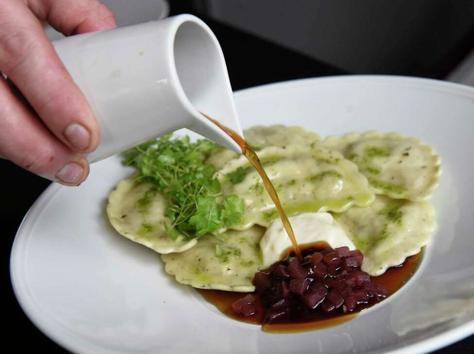 Chef Colin Miner pours an ingredient over lamb agnolotti - mint, pears, celeriac, parsley at Park 26 at The Queensbury Hotel on Thursday, Nov. 14, 2019 in Glens Falls, N.Y. (Lori Van Buren/Times Union)