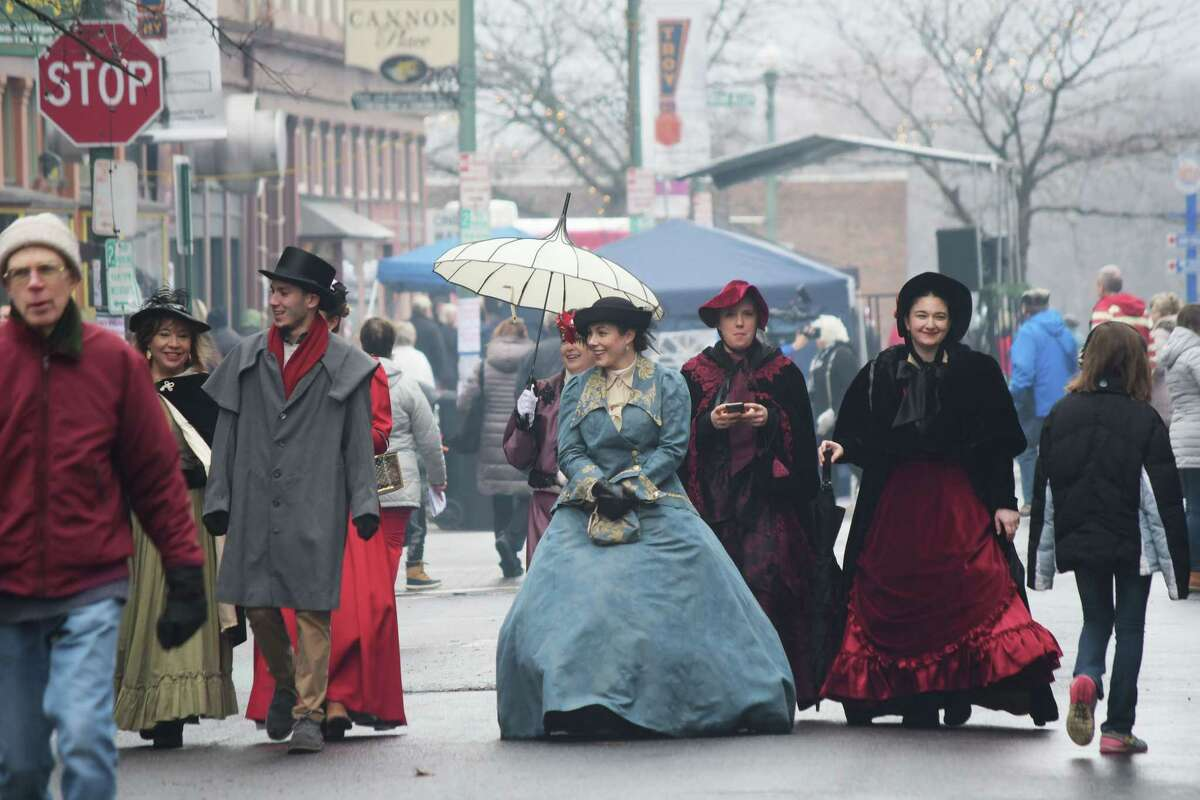 Employees with the Rensselaer County Chamber of Commerce, dressed in period clothing, stroll along the street at the 36th Annual Troy Victorian Stroll on Sunday, Dec. 2, 2018, in Troy, N.Y. The chamber of commerce manages the stroll. (Paul Buckowski/Times Union)