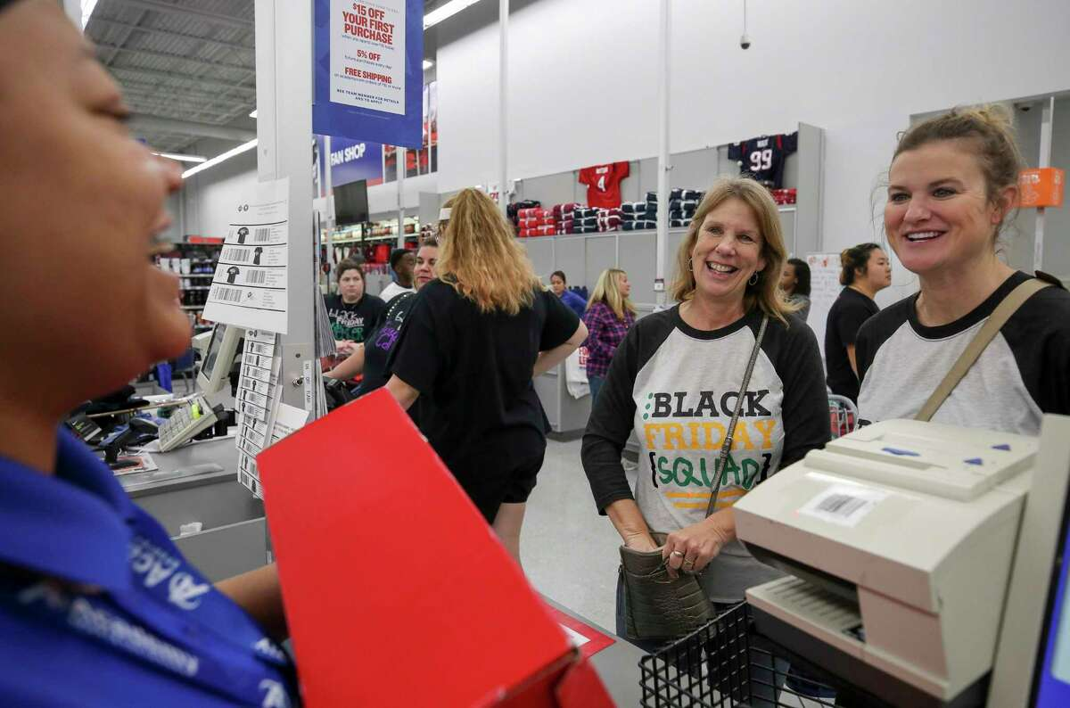 Nancy Conway, 58, and her daughter Amy Clepper, 35, check out after shopping at Academy Sports and Outdoor during Black Friday on Friday, Nov. 29, 2019, in Cypress, Texas.