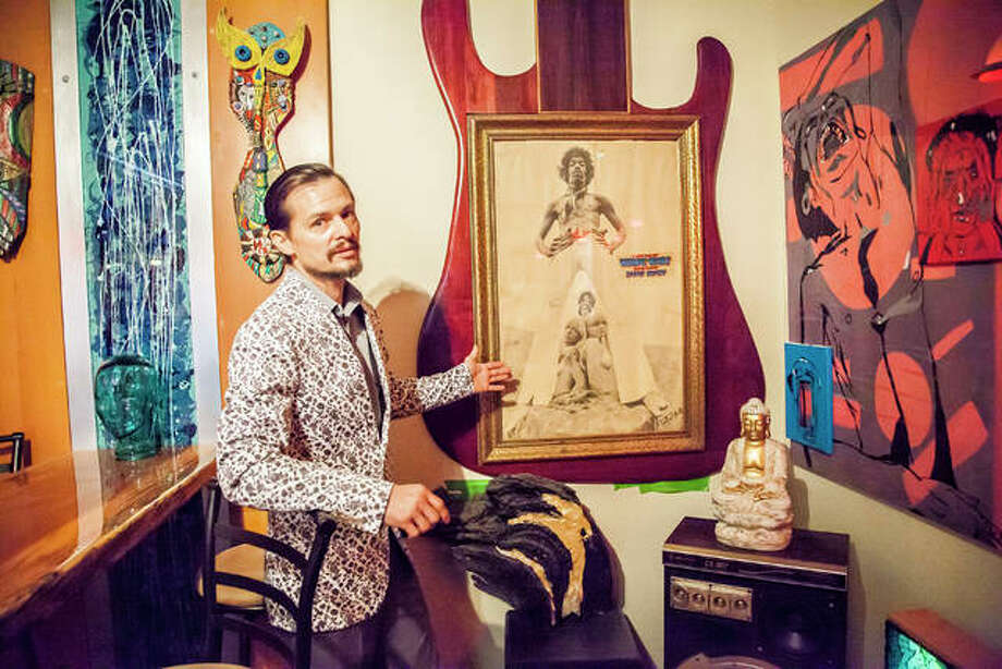 Artist Michael Snider at his home in Alton, standing next his single greatest possession, a 1967 Jimi Hendrix poster signed by photographer Ron Raffaelli. Photo: Jeanie Stephens|The Telegraph