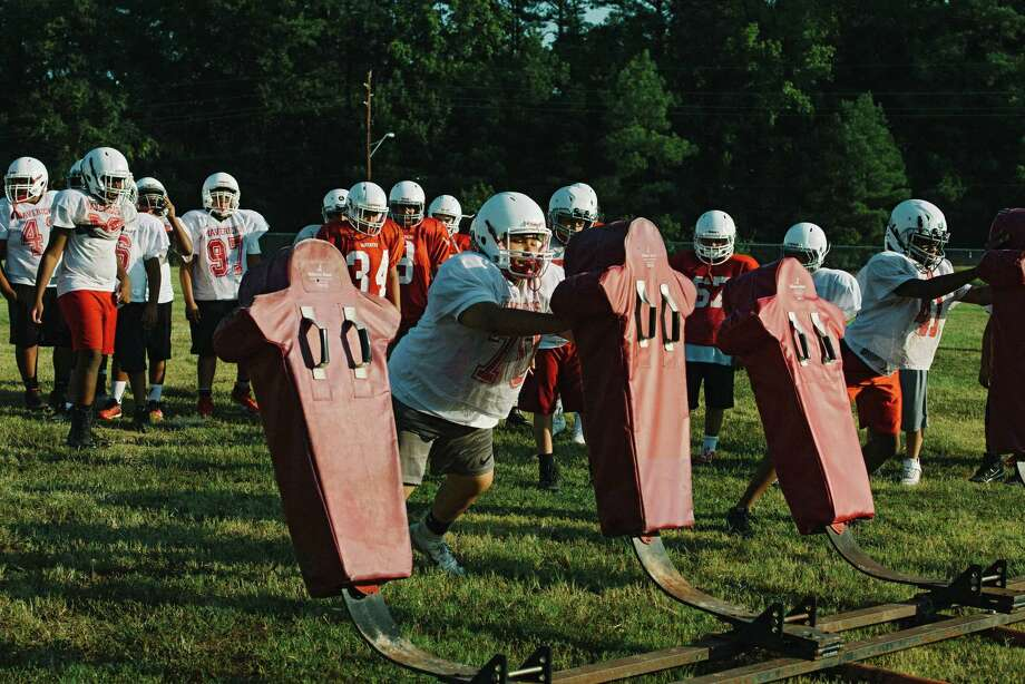 Marshall High School junior varsity football players hit the tackling sled during a morning workout, in Marshall, Texas, Sept. 16, 2019. High school participation in football has dropped more than 10 percent in the past decade, even in football hotbeds like Texas, Ohio and Florida, but the game is a powerful, cultural force in Marshall, where high school games can draw half of the city's roughly 2,400 residents. (Brandon Thibodeaux/The New York Times) Photo: BRANDON THIBODEAUX / Photos By Brandon Thibodeaux / New York Times / NYTNS