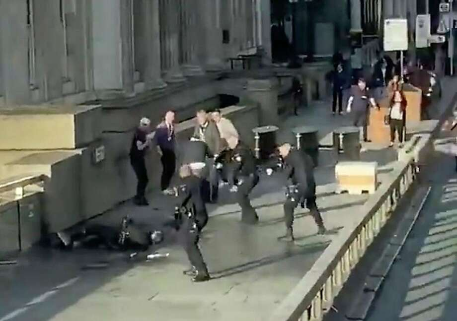 An image from video shows the suspected attacker surrounded by police officers on London Bridge. Photo: @HLOBlog
