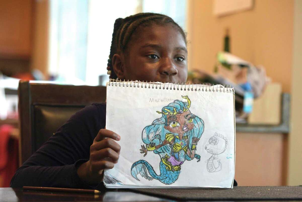 Chelsea Phaire, 10, of Danbury, show one of her favorite drawings she has don. Phaire has started a charity where she gives art kits to children in shelters and to those affected by mass shootings. She went to El Paso, Texas, in October, to hand out 130 art kits to elementary school students in the wake of a mass shooting in that city. Tuesday, November 19, 2019, Danbury, Conn.