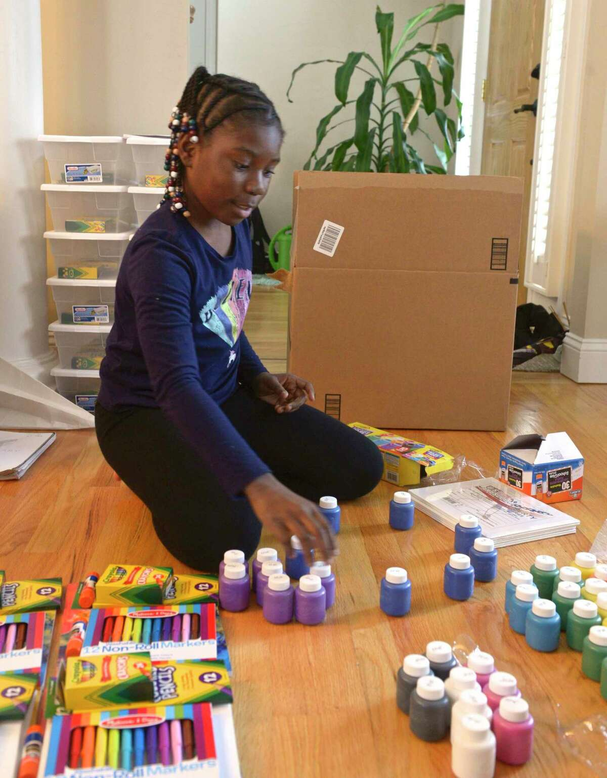 Chelsea Phaire, 10, of Danbury, sorts art supplies for charity she has started where she gives art kits to children in shelters and those affected by mass shooting. She went to El Paso, Texas, in October, to hand out 130 art kits to elementary school students in the wake of a mass shooting in that city. Tuesday, November 19, 2019, Danbury, Conn.