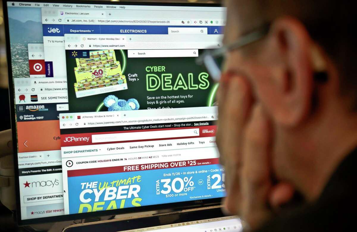 A journalist looks at a computer screen with webpages arranged to show Cyber Monday deals by various online retailers in this 2018 photo. In the whir of holiday shopping hoopla, it can be easy to click a scam link, get duped by fake reviews or leave your personal information unprotected. But there are ways you can come out of the holiday season as both your family's best gift-giver and the most savvy online shopper.
