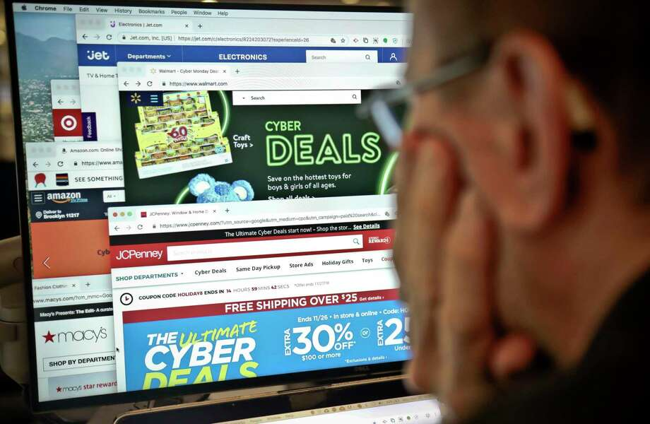 A journalist looks at a computer screen with webpages arranged to show Cyber Monday deals by various online retailers in this 2018 photo. In the whir of holiday shopping hoopla, it can be easy to click a scam link, get duped by fake reviews or leave your personal information unprotected. But there are ways you can come out of the holiday season as both your family's best gift-giver and the most savvy online shopper. Photo: Bebeto Matthews /Associated Press File Photo / Copyright 2018 The Associated Press. All rights reserved.