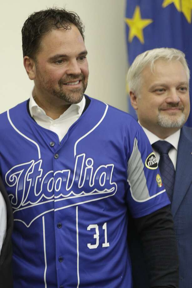 Hall of Fame catcher Mike Piazza shows his jersey during his presentation as Italy's national baseball team coach, at the Italian Olympic Committee headquarters in Rome, Friday, Nov. 29, 2019. At left is the President of the Italian Baseball Federation Andrea Marcon. (AP Photo/Alberto Pellaschiar) Photo: Alberto Pellaschiar / Associated Press