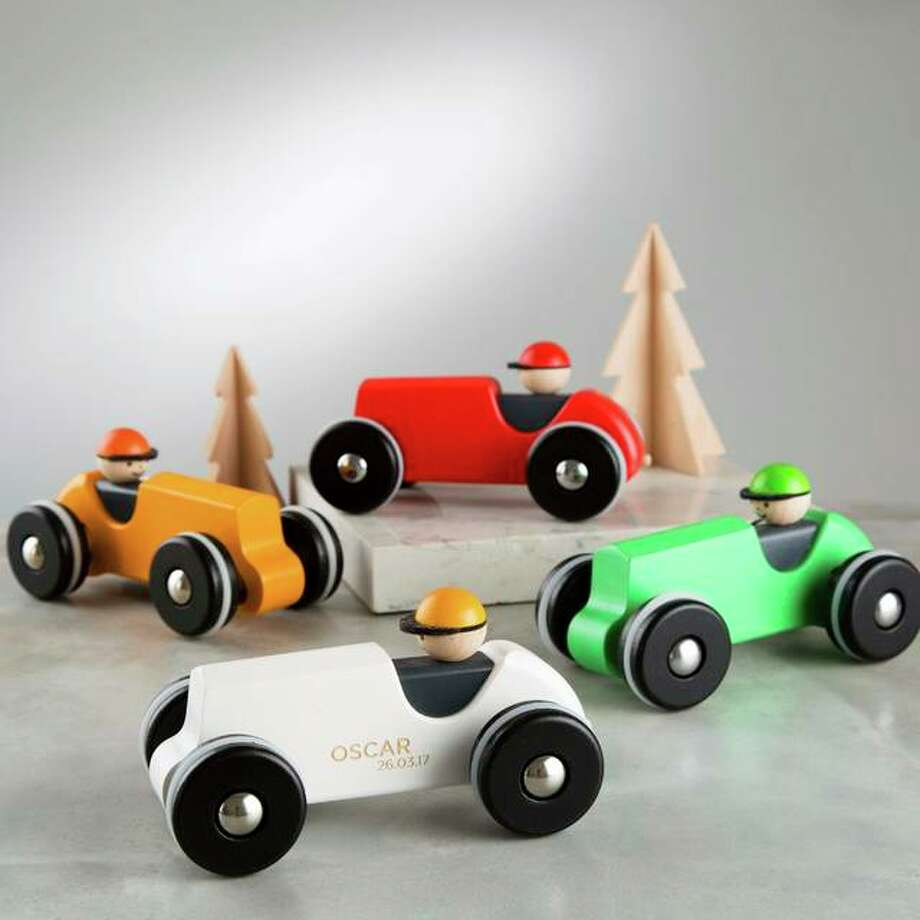 This image released by Etsy shows wooden racing car that can be engraved with a child's name and a special date from Etsy seller TwentySevenUK. The seller offers free shipping to the U.S. Each car is $43.05 and comes in white, yellow or green. (Stsy via AP)