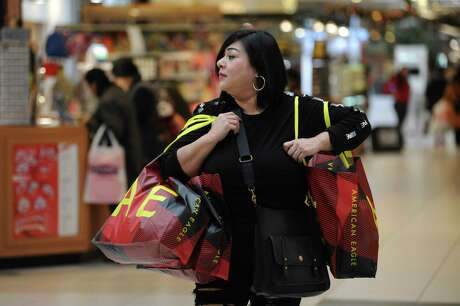 Anna Saldaña carries Christmas gift items purchased at American Eagle at South Park Mall on Black Friday, Nov. 29, 2019.