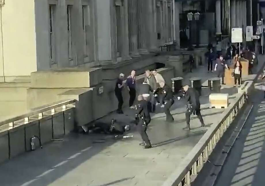 In this grab taken from video made available by @HLOBlog, a man is surrounded by police after an incident on London Bridge, in London, Friday, Nov. 29, 2019. A man wearing a fake explosive vest stabbed several people before being tackled by members of the public and then shot dead by armed officers on London Bridge, police and the city's mayor say. Police say they are treating it as a terrorist attack. (@HLOBlog via AP) Photo: Associated Press
