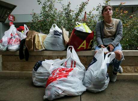 Maritza Rosales, 19, waits for her mother to return from a store, next to the dozen or so bags of items purchased during Black Friday at the Houston Premium Outlets Friday, Nov. 29, 2019, in Cypress, Texas.