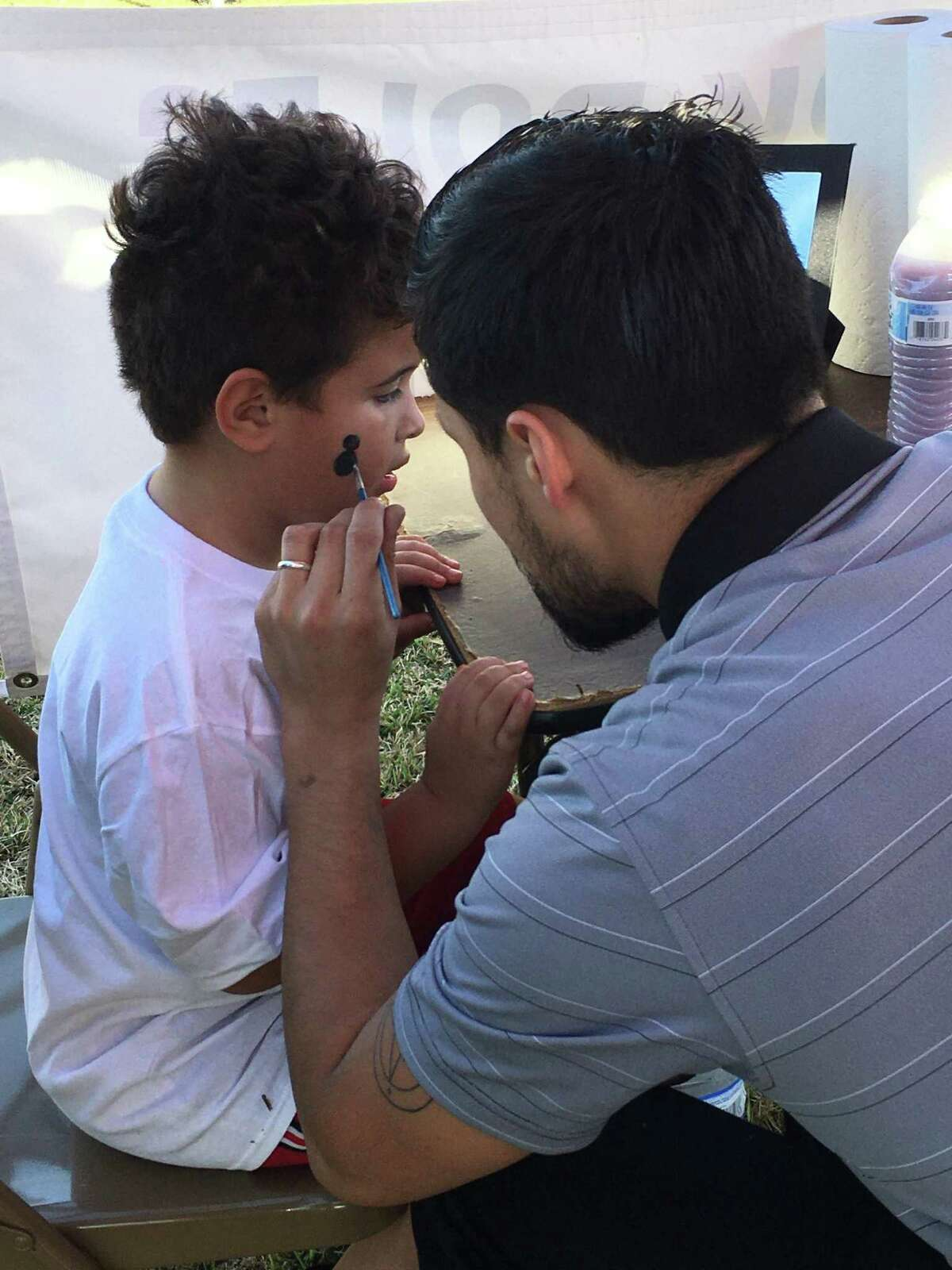 Adrian Morales, 4, has his face painted by Max Dalton at the fourth annual Richmond Pecan Harvest Festival. Jennifer Morales, Adrian's mom, said this year's festival was a big improvement over last year when the weather turned cold and rainy.