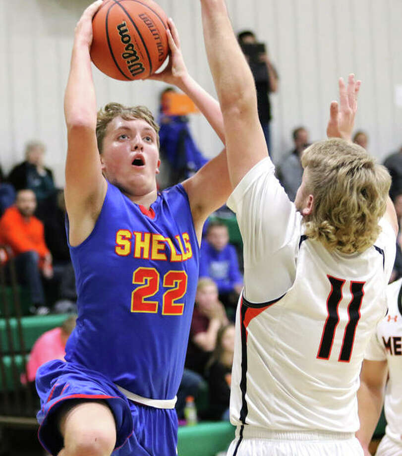 Roxana's Jake Golenor (22) drives and shoots over Marissa's Blake Steinwagner during the first half Friday night at the Metro-East Lutheran Tournament in Edwardsville. Photo: Greg Shashack / The Telegraph