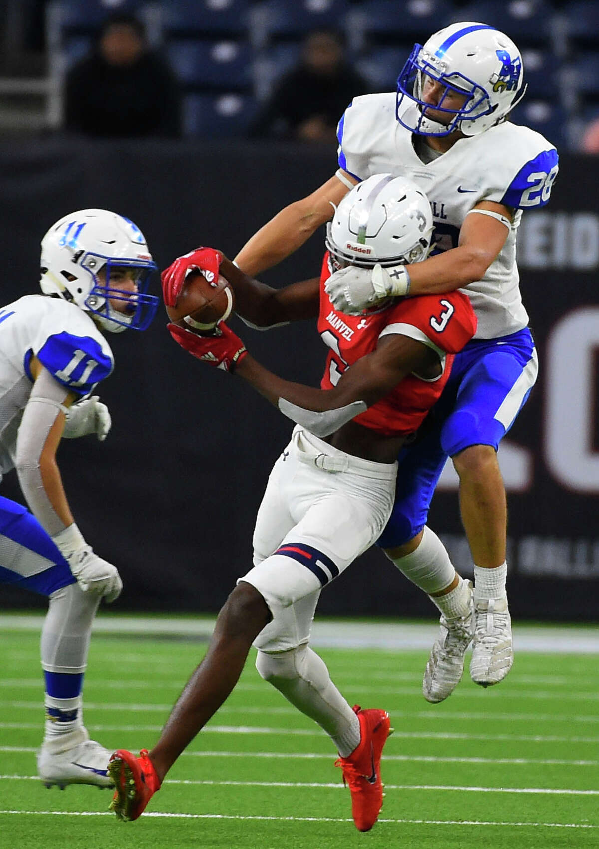 Manvel wide receiver Jalen Walthall (3) catches a pass as Barbers Hill defensive back Josh Bishop defends during the second half of a 5A Division II regional high school football playoff game, Friday, Nov. 29, 2019, in Houston.