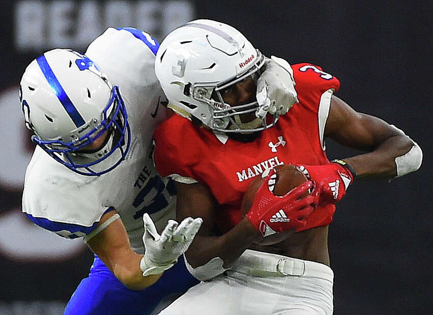 Manvel wide receiver Jalen Walthall, right, is tackled by Barbers Hill defensive back Josh Bishop during the second half of a 5A Division II regional high school football playoff game, Friday, Nov. 29, 2019, in Houston.