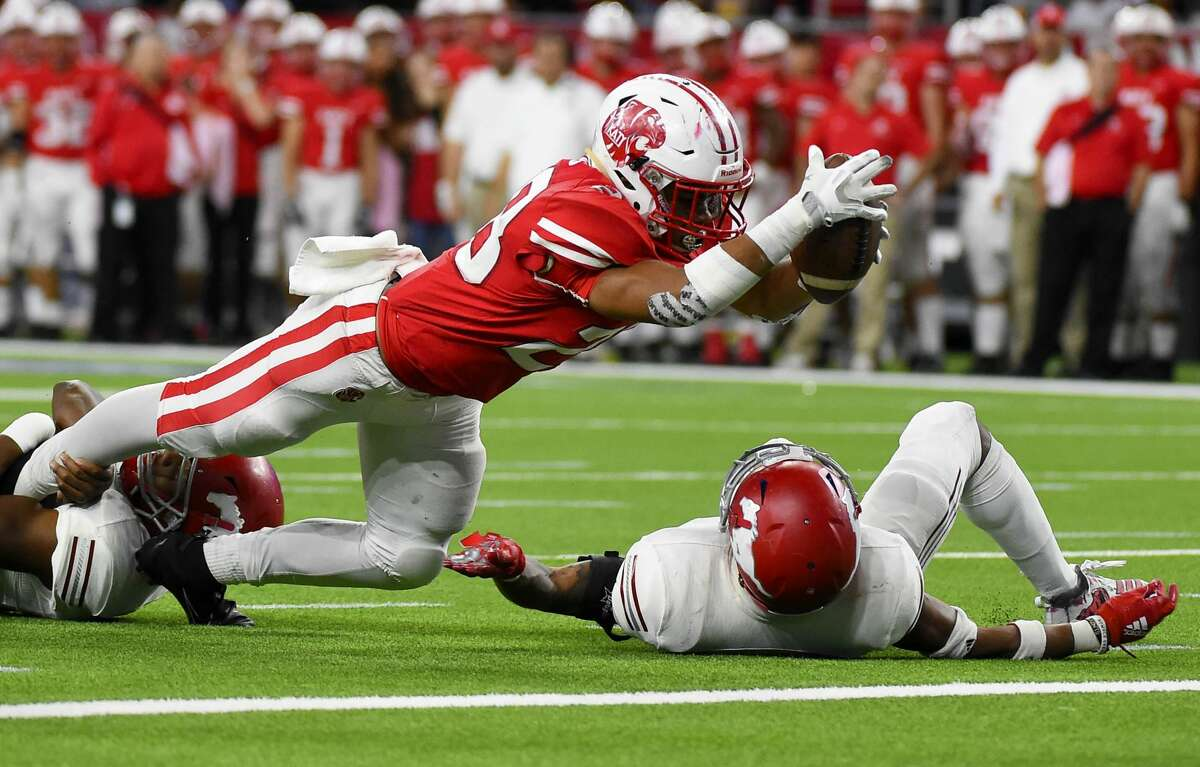 Katy running back Jalen Davis, center, dives into the end zone for a touchdown during the second half of a 6A Division 1 regional high school football playoff game against North Shore, Friday, Nov. 29, 2019, in Houston.