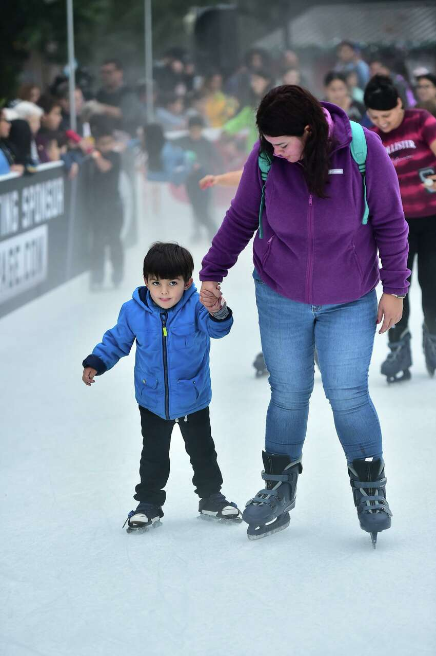 Carlos Gonzalez and his mother, Nancy Gonzalez, skate at the Rotary Ice Rink during the 35th annual H-E-B Tree Lighting Celebration in Travis Park on Friday.
