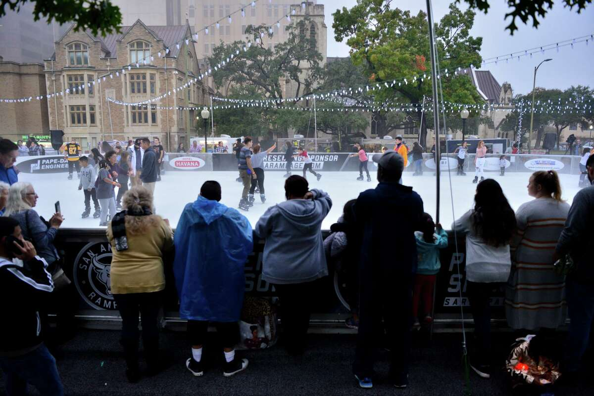 People watch skaters at the Rotary Ice Rink during the 35th annual H-E-B Tree Lighting Celebration in Travis Park on Friday. Visitors waited in line for up to three hours for a chance to skate on the ice.