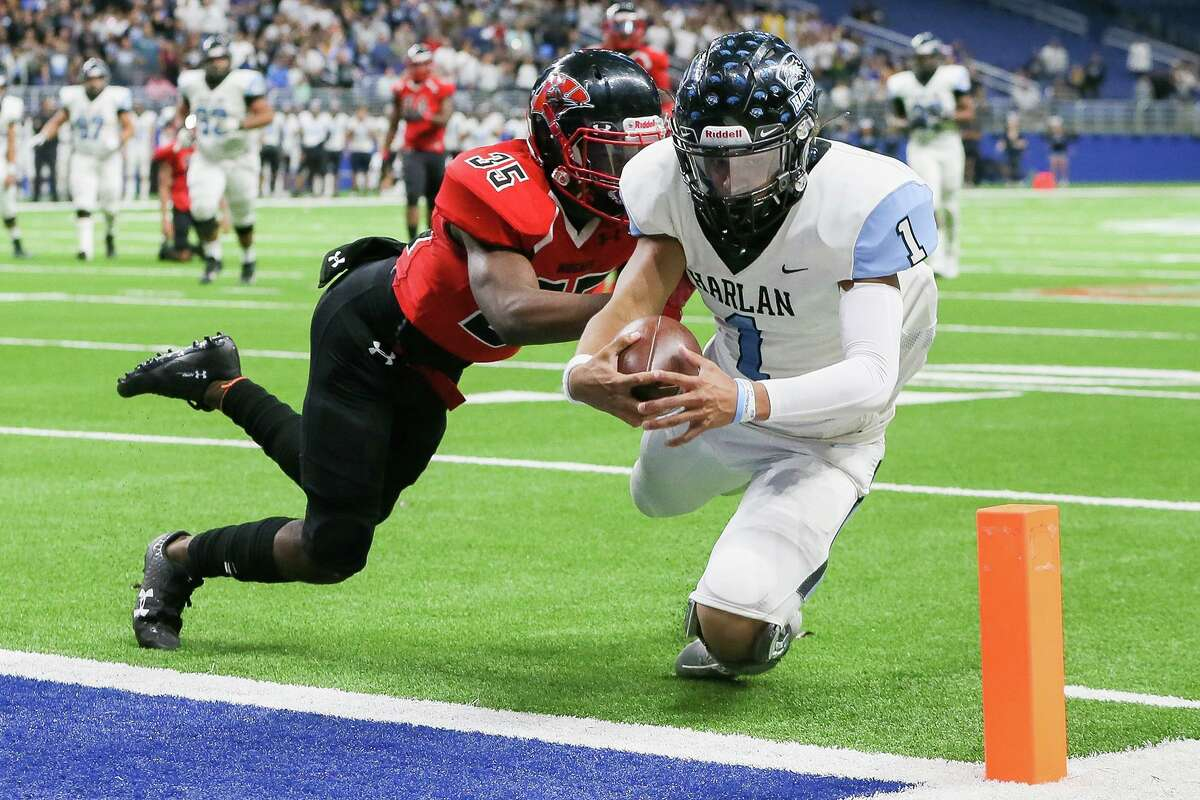 Harlan quarterback Kannon Williams scores on a 17-yard run as Wagner's Amani Roberts tries to stop him during the first half of their third round Class 5A Division I high school football playoff game at the Alamodome on Friday, Nov. 29, 2019.