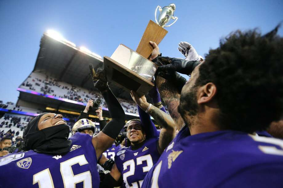 The Huskies hoist the Apple Cup trophy after toppling Washington State 31-13 on Friday. Photo: Abbie Parr/Getty Images / 2019 Getty Images