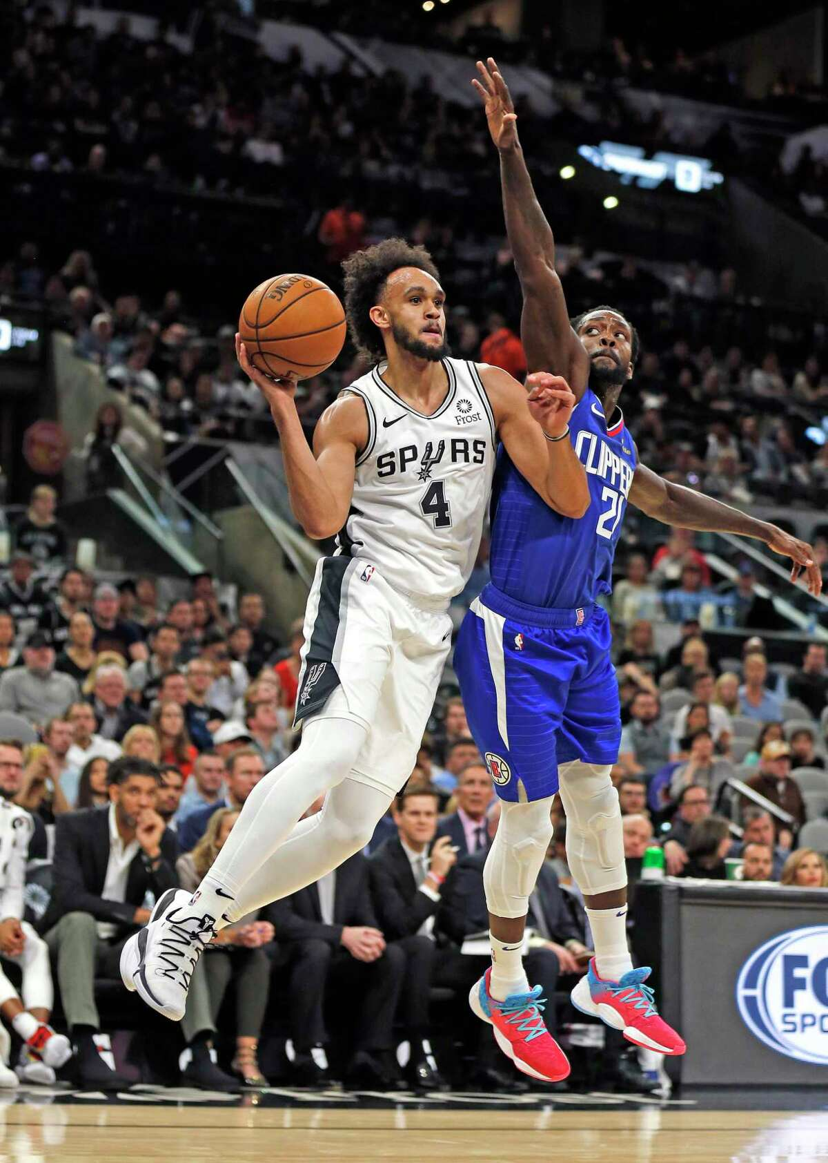 Derrick White #4 of the San Antonio Spurs passes off after being guarded by Kawhi Leonard #2 #2 of the Los Angeles Clippers in the first half of the game between the San Antonio Spurs and the Los Angeles Clippers on Friday, November 29,2019 at AT&T Center
