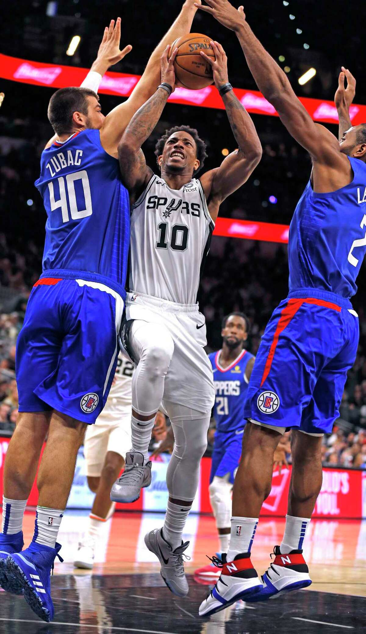 DeMar DeRozan #10 of the San Antonio Spurs drives between Ivica Zubac #40 of the Los Angeles Clippers and Kawhi Leonard #2 in the first half of the game between the San Antonio Spurs and the Los Angeles Clippers on Friday, November 29,2019 at AT&T Center.