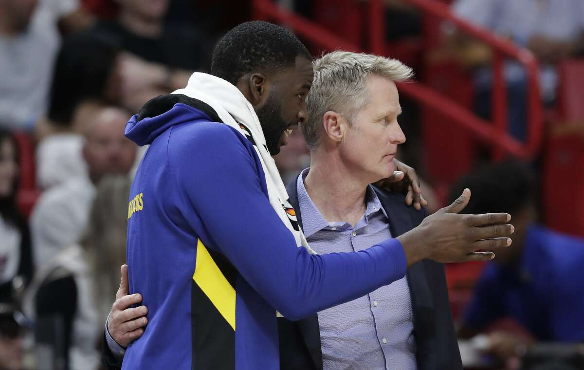 Golden State Warriors forward Draymond Green, left, talks with head coach Steve Kerr during the second half of an NBA basketball game against the Miami Heat, Friday, Nov. 29, 2019, in Miami. (AP Photo/Lynne Sladky)