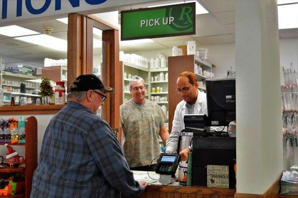 Brian McCaffery, center, and Paul Yenduri, right, fill a prescription for Bert Wood, left, at the Sanford Family Pharmacy Tuesday. (Ashley Schafer/Ashely.Schafer@hearstnp.com)