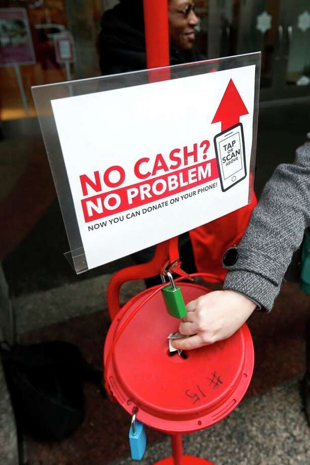 In this Nov. 15 photo, a shopper donates cash to the Salvation Army's annual holiday red kettle campaign, with a reminder that mobile contributions are also excepted on Chicago's Magnificent Mile. Cashless shoppers have a new option to give to the Army's red kettle campaign this year using their smartphone. Leaders hope adding Apple and Google payment options will boost fundraising to the campaign, which makes up 10% of The Salvation Army's annual budget. Those donations fund programs providing housing, food and other support to people in poverty. (AP Photo/Charles Rex Arbogast) / Copyright 2019 The Associated Press. All rights reserved