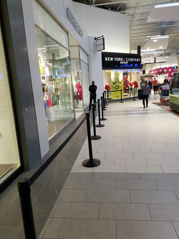 Katy Mills Mall security guardCasimir Onyilinba watches over an empty stanchion line outside the Michael Kors store. Photo: Claire Goodman / Staff Writer