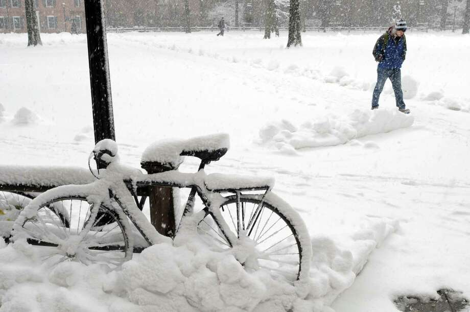 In this 2013 file photo, a student at Yale University in New Haven, Connecticut uses his feet as transportation on the Old Campus as a bicycle nearby, covered by snow, sits idle during a snowstorm in March. Photo: Peter Hvizdak / Hearst Connecticut Media / ©Peter Hvizdak /  New Haven Register