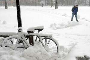 In this 2013 file photo, a student at Yale University in New Haven, Connecticut uses his feet as transportation on the Old Campus as a bicycle nearby, covered by snow, sits idle during a snowstorm in March.
