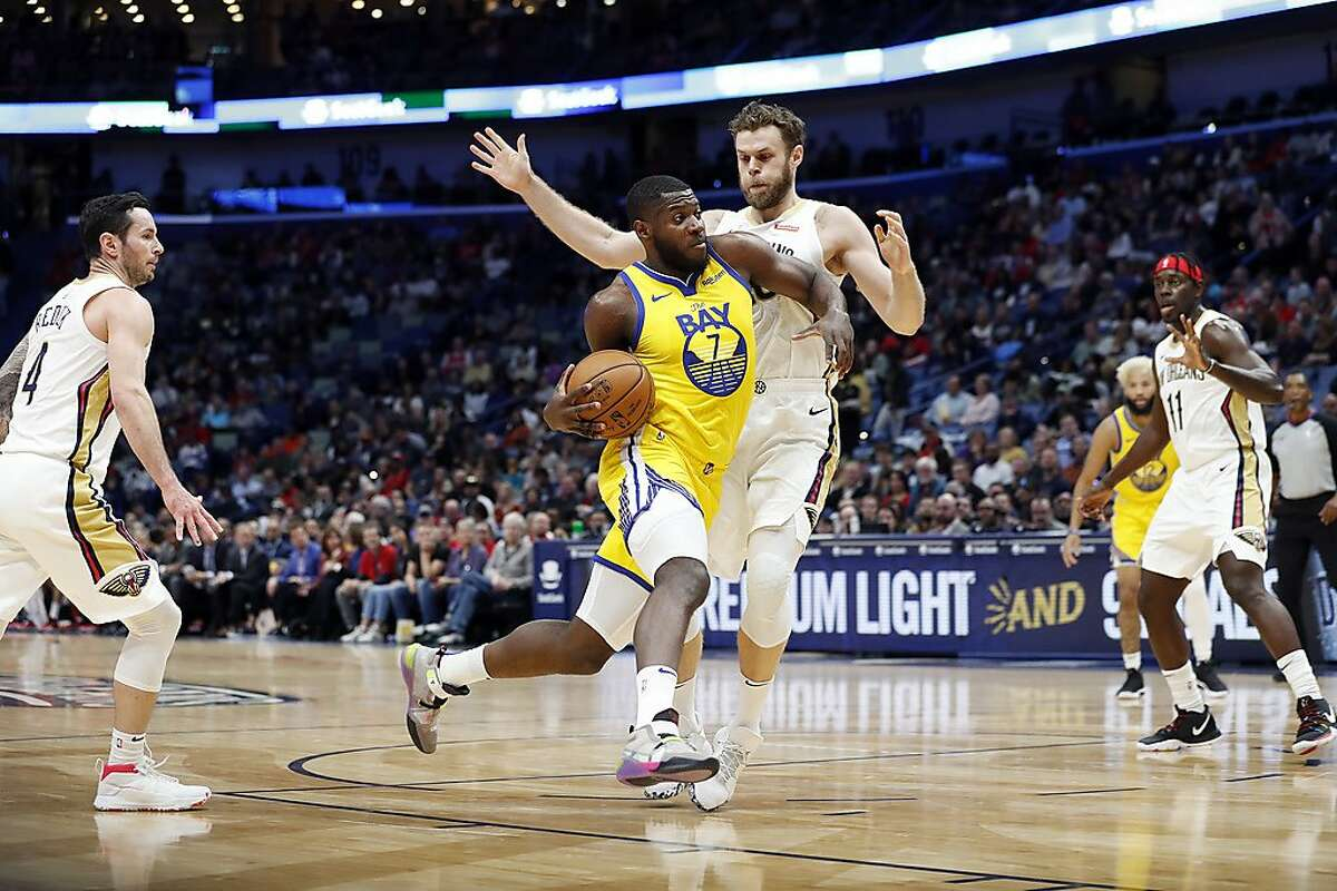 Golden State Warriors forward Eric Paschall (7) and New Orleans Pelicans forward Nicolo Melli (20) in the first half of an NBA basketball game in New Orleans, Sunday, Nov. 17, 2019. (AP Photo/Tyler Kaufman)